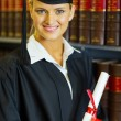 Happy female graduate in university library — Stock Photo
