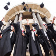 Graduates throwing graduation hats — Stock Photo #42492401