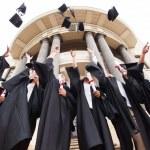 Graduates throwing graduation hats — Stock Photo