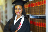 African female graduate in library — Stock Photo