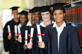 Graduates standind in row and holding diploma — Stock Photo
