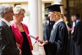 Female graduate talking to parents — Stock Photo