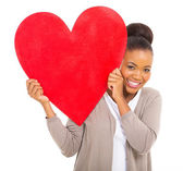 Happy african woman holding red heart symbol — Stock Photo