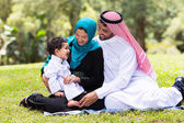 Muslim family sitting outdoors — Stock Photo