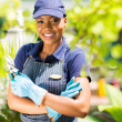 African nursery worker holding garden tool — Stock Photo