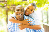 African woman enjoying piggyback ride on boyfriend — Stock Photo