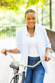 Young african american woman walking with a bike — Stockfoto