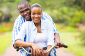 African couple riding bicycle together — Foto de Stock