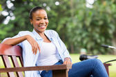 Young african woman sitting outdoors — Stock Photo