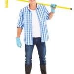 Man carrying a garden rake — Stock Photo