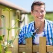 Man standing by garden fence — Stock Photo