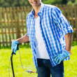 Man standing with lawnmower — Stock Photo