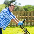 Man pushing lawnmower — Stock Photo