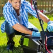 Man emptying lawnmower grass catcher — Stock Photo #46007881