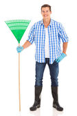 Man holding a rake — Stock Photo