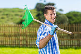 Man with fan rake — Stock Photo