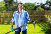 Man with a hoe in garden — Stockfoto