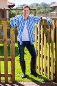 Man standing at garden gate — Stockfoto