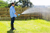 Man watering backyard lawn — Foto Stock