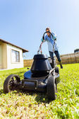 Male gardener pushing electric lawnmower — Stock Photo