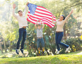 American family jumping with USA flag — Stock Photo
