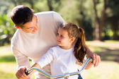 Father riding bicycle with daughter — Stock Photo