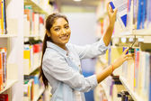 Indian student pulling book off shelf — Stock Photo