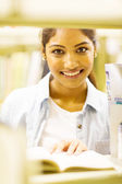 Female indian student behind bookshelf — Stock Photo