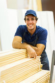 Worker leaned on stacked wood — Stock Photo