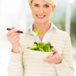 Middle aged woman eating salad — Stock Photo