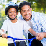 Man helping son ride bike — Stock Photo #49178585