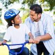 Father helping daughter ride bicycle — Stock Photo #49179313