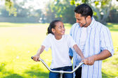 Father teaching daughter ride bicycle — Stock Photo