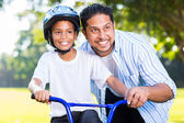 Man helping son ride bike — Stock Photo