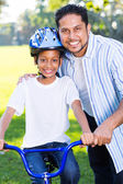 Girl on bike with father — Stock Photo