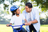 Father helping daughter ride bicycle — Stock Photo