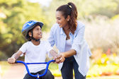 Mother help son ride bicycle — Stock Photo