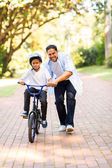 Father teaching son to ride bicycle — Stock Photo
