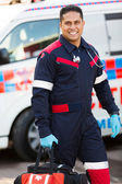 Paramedic carrying portable equipment — Stockfoto
