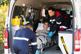 Emergency medical staff transporting patient — Stockfoto