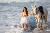 Young woman walking with horse — Stock Photo