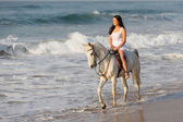 Lady riding horse on beach — Stock Photo