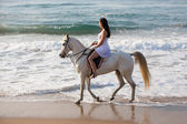 Woman horse rider on beach — Stock Photo