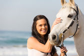 Happy woman comforting her horse — Stock Photo
