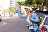 Female tourist hailing for cab — Stock Photo
