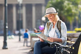 Young tourist looking at map — Stock Photo
