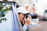 Tourists photographing city from car — Stock Photo
