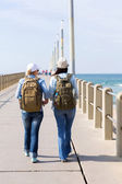 Female travelers walking on pier — Stock Photo