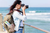 Young tourist photographing at beach — Stock Photo