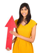 Indian girl holding direction arrow pointing up — Stock Photo